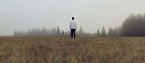elegancko ubrany mężczyzna stoi w polu - czym jest siła mężczyzny